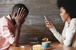 Annoyed and unhappy African man sitting with angry look, resting elbows on table while his smiling girlfriend texting her friends via social networks on mobile phone, instead of talking to him