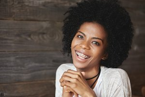 People and happiness concept. Cheerful African American young woman smiling at camera showing her ultrawhite teeth with braces. Black girl with Afro hairstyle posing against wooden wall background