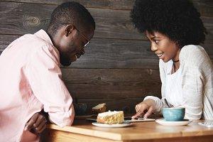 Two dark-skinned people sitting at cafe, laughing and having fun while using tablet together: girl with Afro haircut pointing at tablet screen, showing something interesting or funny to her friend