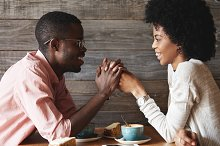 Dark-skinned young couple sitting at restaurant: black man in glasses holding his girlfriend's hands, declaring his love to her or proposing on their anniversary day, both looking happy and cheerful