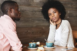 Two young black smart managers discussing very important question sitting at coffee shop, searching for new brilliant idea for developing strategy of successful business, woman having thoughtful look