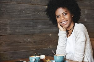 Human emotions and feelings. Young attractive and charismatic dark-skinned woman with curly hair, wearing casual clothes, drinking coffee with cake posing with big smile showing her teeth in braces