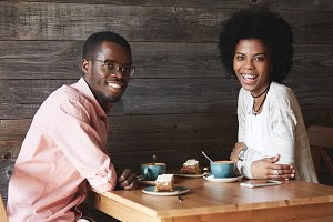 Indoor portrait of happy young African American students sitting at cafeteria having desserts and coffee looking with sincere smile. Black handsome man talking to his beautiful female college mate