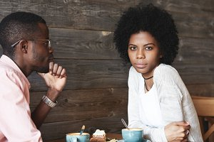 Young African couple in love sitting at coffee shop: man in glasses admiring his girlfriend with gentle look, woman looking at camera with thoughtful expression. Old friends spending time together