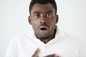 Close up portrait of young dark-skinned student or employee looking at camera with surprised guilty expression, after doing something wrong, holding hand on chest, shocked with something he just heard