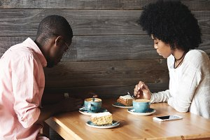 Two black co-workers having launch together during coffee break. Young African man in glasses using smartphone while sitting at cafe with his dark-skinned girlfriend drinking tea and eating cakes