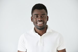 Cropped shot of smiling handsome young casually dressed African man model in white polo shirt, smiling showing his teeth, against studio background with copy space for your promotional information