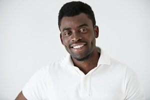 Headshot of handosme happy young African man dressed in white polo shirt, looking cheerful, smiling, showing his white teeth, posing against studio wall background. Human face expressions and emotions