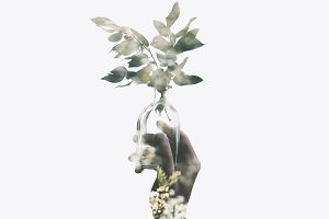 Double exposure of hand with flower