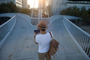 Man on pedestrian bridge with tablet