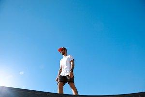 Hipster in a skate park against blue sky
