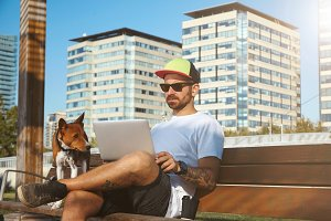 Hipster with laptop, coffee and dog
