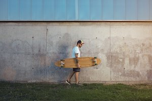 Tattooed man with longboard next to a concrete wall