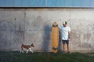 Longboarder with basenji dog next to gray concrete wall
