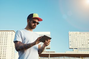 Tattooed bearded young man with a tablet in  city