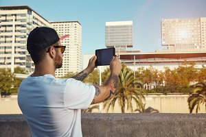Young man taking photos with tablet in a city