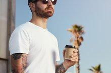Tattoed man in blank t-shirt with paper coffee cup