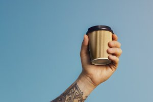 Blank paper coffee cup in tattooed man's hand