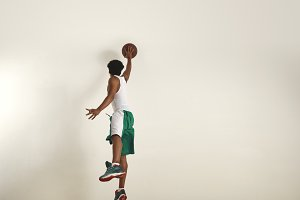 Back of a jumping basketball player shooting  ball