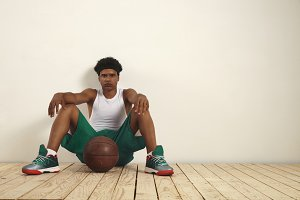 Tired basketball player sitting on the floor against the wall