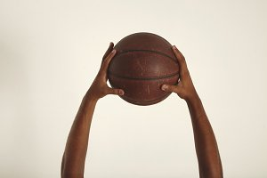 Two hands hold a vintage basketball