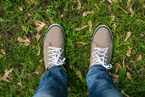 Man feet in shoes on grass