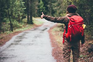 Woman with red backpack hitchhiking
