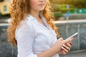 teen girl standing with mobile phone