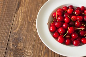 plate with fresh red cherries
