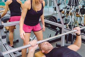 Woman coach screaming to man in bench press training