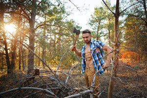 Lumberjack with an ax chop branches