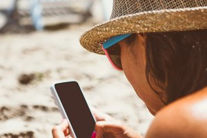 Woman in hat uses phone on the beach