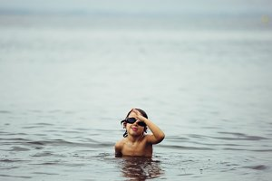 Child making faces playing in sea