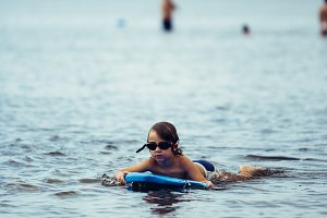 Boy with bodyboard in sea