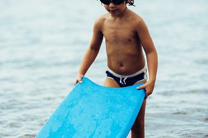 Boy with bodyboard in sea