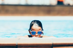 Child in sunglasses by the pool