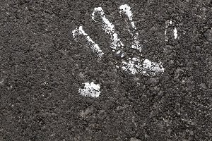 A handprint painted white on asphalt