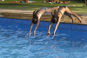 Two girls are thrown into a pool