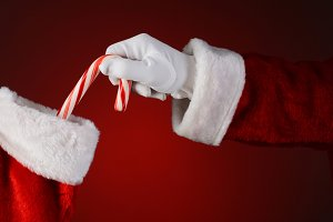 Santa Placing Candy Cane in Stocking
