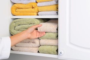Woman Taking Towel From Linen Closet