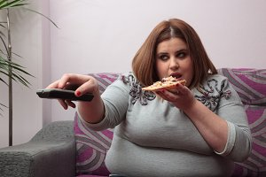 Woman zapping and eating pizza
