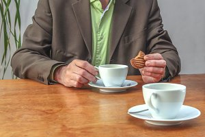 Man drinking coffee and eating cooki