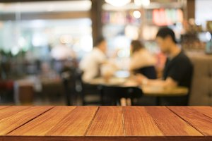 Wood table top on blur coffee shop
