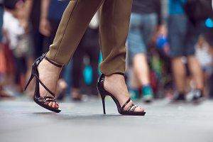 Woman feet making step on city