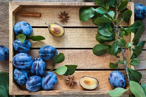 Fresh plums in wooden box.