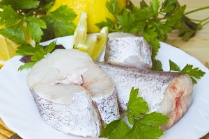 Hake dish with parsley and lemon on wooden background