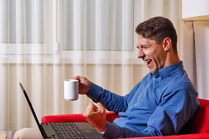 Man works for laptop. joy success.