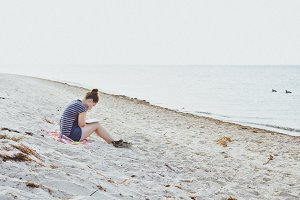 Girl Reading a Book at the Beach