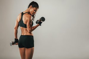 Fit strong young woman lifting