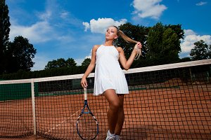 woman in a tennis suit and racket
